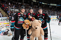 KELOWNA, CANADA - DECEMBER 1:  Leif Mattson #28, Lassi Thomson #2 and Kyle Topping #24 of the Kelowna Rockets stand on the ice with the teddy bears after the annual toss against the Saskatoon Blades on December 1, 2018 at Prospera Place in Kelowna, British Columbia, Canada.  (Photo by Marissa Baecker/Shoot the Breeze)