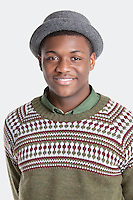 Portrait of a happy African American man wearing hat over gray background