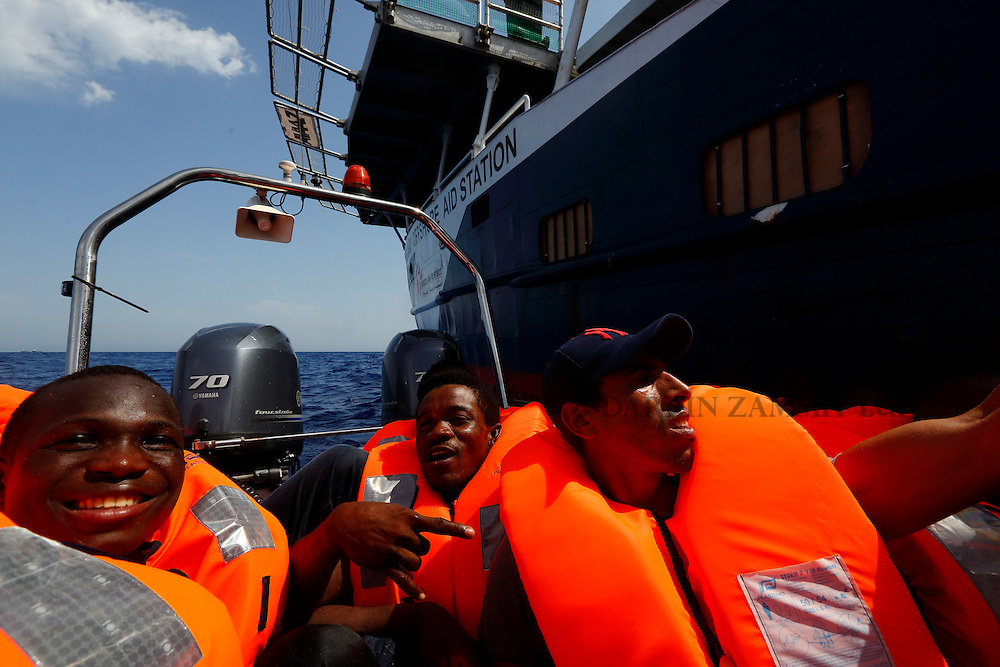 Migrants sit in a Migrant Offshore Aid Station (MOAS) RHIB (Rigid-hulled inflatable boat) as they arrive alongside the MOAS ship MV Phoenix some 20 miles (32 kilometres) off the coast of Libya, August 3, 2015.  118 migrants were rescued from a rubber dinghy off Libya on Monday morning . The Phoenix, manned by personnel from international non-governmental organisations Medecins san Frontiere (MSF) and MOAS, is the first privately funded vessel to operate in the Mediterranean.<br /> REUTERS/Darrin Zammit Lupi <br /> MALTA OUT. NO COMMERCIAL OR EDITORIAL SALES IN MALTA