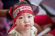 """10 MAY 2010 - BANGKOK, THAILAND: A Thai child with a Red Shirt head band in the crowd at a memorial service Monday. The Red Shirts held a special memorial service at their main protest site in Ratchaprasong Intersection Monday with Buddhist monks leading chants to mark the one month anniversary of the street violence on April 10 that left 25 dead and more than 800 injured. Thai media is reporting that Prime Minister Abhisit Vejjajiva has given the Red Shirts has given the Red Shirts until the end of today to either accept his """"Road Map for Reconciliation"""" and end the protest or face unspecified consequences widely thought to include a military crackdown.   Photo by Jack Kurtz / ZUMA Press"""