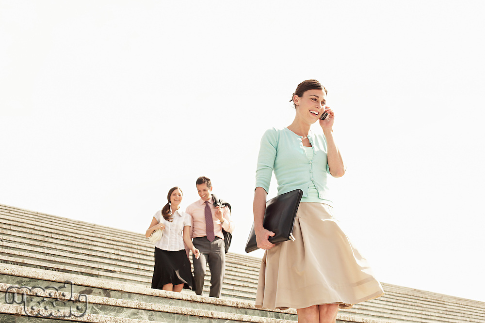 Three office workers walking down steps woman in foreground using mobile phone low angle view.