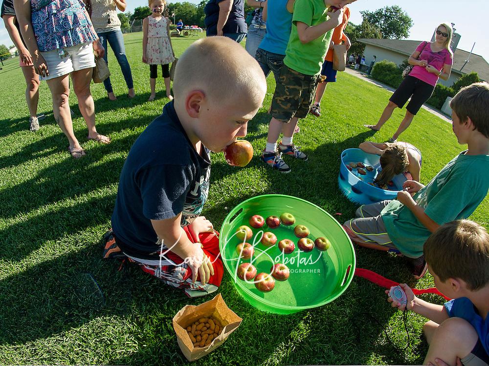 Darius Mandigo-Seavey bobs for apples during Opechee Day Camp's Peanut Festival Thursday evening.  (Karen Bobotas/for the Laconia Daily Sun)