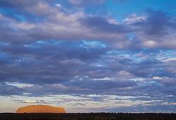 Australia, Northern Territory, Uluru-Kata Tjuta National Park, Ayer's Rock (also known as Uluru) glows red under dramatic clouds
