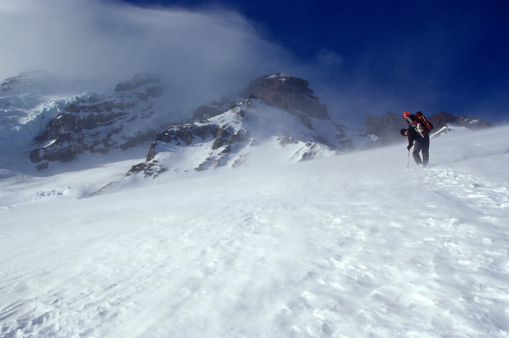 A climber hikes up the Muir Snowfield through high winds and spindrift on his way to Camp Muir at 10,000 feet on Mt. Rainier.