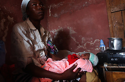 Rosianne Moliere(left) holds her un-named 3 day old nephew, just 3 days after his mother, Kele Tintin,  was caught in the middle of gang warfare and killed on her way to work.  Tintin stayed alive long enough to give birth to a son the same day, and died 6 hours later.    The security situation in Cite-Soleil, one of the most dangerous slums in Haiti,  has deteriorated over the past few months with two warring gangs controlling the entire town.  In Project, the side of town controlled by a pro-aristide gang, the market had to move away from the border zone, people take creaky, wooden boats across the harbor instead of crossing the dividing line, and children are threatened with death if they attempt to cross the line on their way to school.