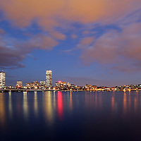 City of Boston skyline photography at twilight showing landmarks such as John Hancock building, Prudential Center and Mass Avenue bridge as seen from Memorial Drive in Cambridge, MA. <br />