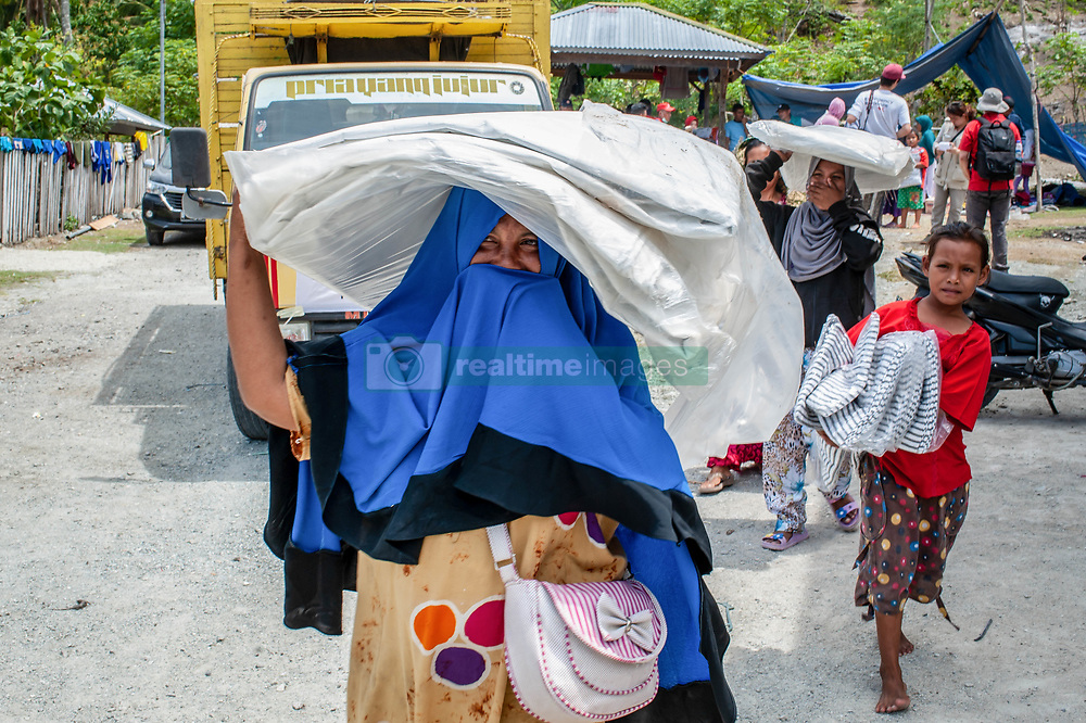 October 7, 2018 - Palu, Central Sulawesi, Indonesia - Refugee victims bring aid at one of the posts set up by NGOs in Donggala..A deadly earthquake measuring 7.5 magnitude and the tsunami wave caused by it has destroyed the city of Palu and much of the area in Central Sulawesi. According to the officials, death toll from devastating quake and tsunami rises to 1,480, around 800 people in hospitals are seriously injured and some 62,000 people have been displaced in 24 camps around the region. (Credit Image: © Hariandi Hafid/SOPA Images via ZUMA Wire)