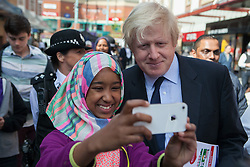 Boris Johnson, Harrow town centre visit. A young girl takes a 'selfie' using a smartphone with the Mayor of London Boris Johnson during a visit meeting local police officers and council staff taking part in Operation Secure Streets, a borough-led crime and anti-social behaviour initiative. St Ann\'s shopping centre, Harrow, United Kingdom. Thursday, 10th April 2014. Picture by Daniel Leal-Olivas / i-Images