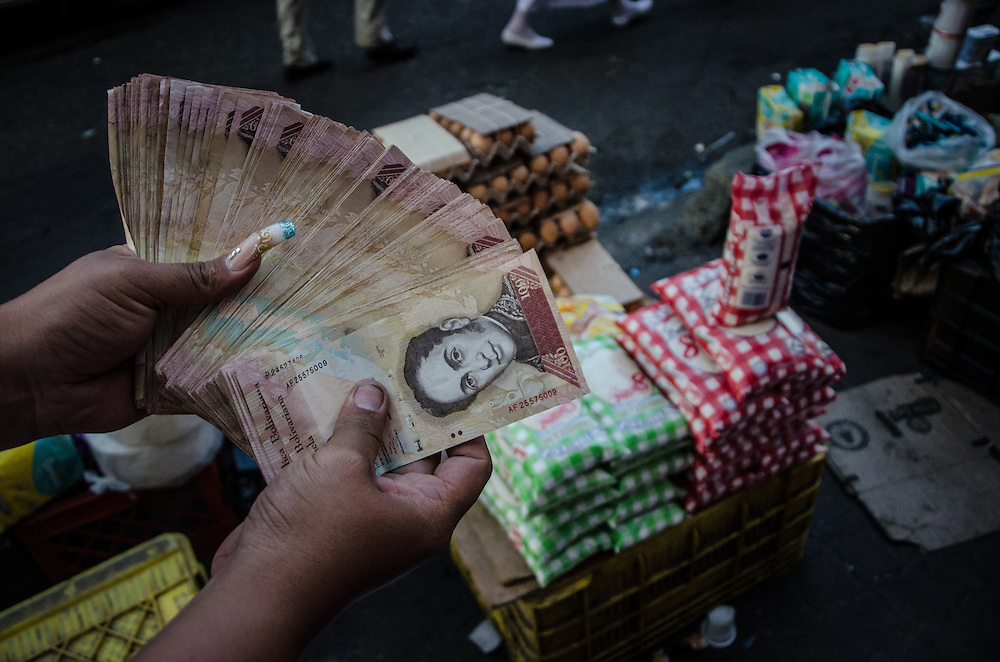 CARACAS, VENEZUELA - JANUARY 14, 2016: A black market vendor shows the money she earned today, illegally re-selling price controlled products. She said she earns approximately 200,000 bolivares a month doing this work -- profits that are well over ten times the minimum wage. Shoppers come to the black market in Petare slum on the outskirts of Caracas to buy hard-to-find products such as soap, shampoo, corn flour, rice, coffee, cooking oil and diapers. All of these items are regulated by government price controls in supermarkets and pharmacies, often times at prices lower than they cost to produce or import -- which leads to shortages. In Petare, vendors illegally re-sell the items at exponentially higher prices, taking advantage of the high demand of hard-to-find products.  PHOTO: Meridith Kohut