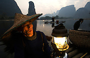 Guilin: Cormorant fishermen emerge at dusk in Yangshuo, amongst scenery of Karst mountains