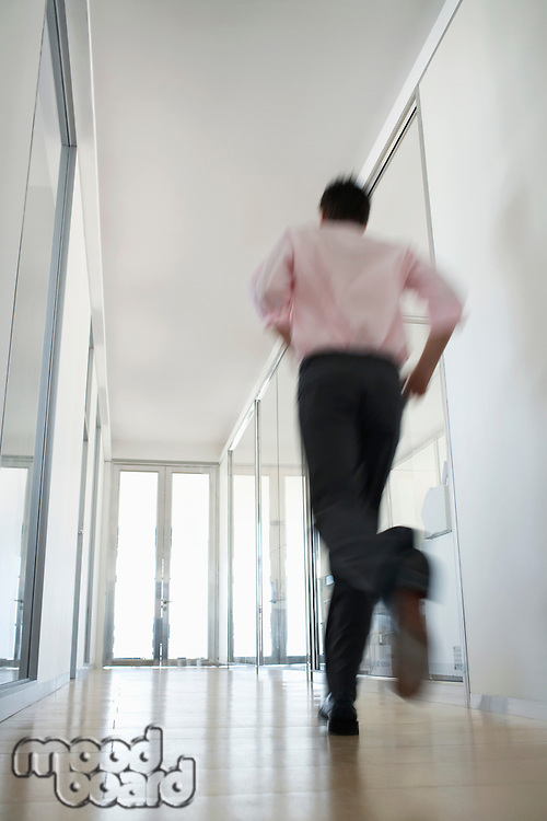 Businessman Running in Corridor low angle back view.