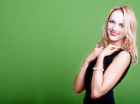 Sexy blonde businesswoman on green background