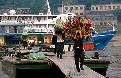CHINA SICHUAN PROVINCE CHONGQUING MAY99 - Dockworkers return from a ferry at the shore of the Yangtse river where it merges with the Jailing river at Chongquing. Seven large cities, including Chongquing, and thousands of villages will be submerged once the water level rises after the completion of the controversial Three Gorges Dam project further downriver. The flooding of areas reaching back more than 550Km upriver will require the evacuation and resettlement of more than 10 million people.  jre/Photo by Jiri Rezac. © Jiri Rezac 1999. . Contact: +44 (0) 7050 110 417. Mobile:  +44 (0) 7801 337 683. Office:  +44 (0) 20 8968 9635. . Email:   jiri@jirirezac.com. Web:     www.jirirezac.com