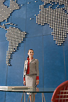 Business woman standing in front of world map in office