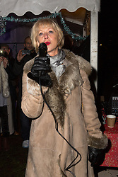 © Licensed to London News Pictures. 08/12/2014. London, UK. Helen Mirren counts down to switching on the Christmas tree lights. Dame Helen Mirren turns on the Christmas tree lights at Wapping Green in Tower Hamlets, East London tonight. This is the first time in many years that Wapping has had a Christmas tree and Dame Helen Mirren surprised residents by turning up at the community event and leading the countdown to switching the tree lights on. She then joined residents singing carols and drinking mulled wine, at the event which was arranged by the local councillor for Wapping and St Katharines, Julia Dockerill. Photo credit : Vickie Flores/LNP