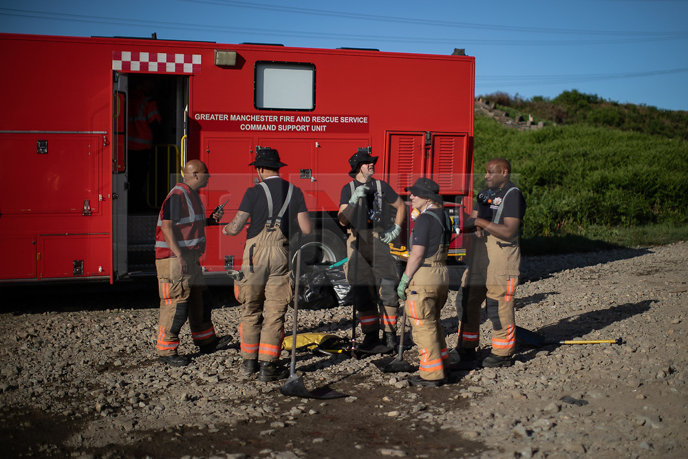 """© Licensed to London News Pictures . 28/06/2018 . Saddleworth , UK . Firefighters at Higher Swineshaw Reservoir . The army are being called in to support fire-fighters , who continue to work to contain large wildfires spreading across Saddleworth Moor and affecting people across Manchester and surrounding towns . Very high temperatures , winds and dry peat are hampering efforts to contain the fire , described as """" unprecedented """" by police and reported to be the largest in living memory . Photo credit: Joel Goodman/LNP"""