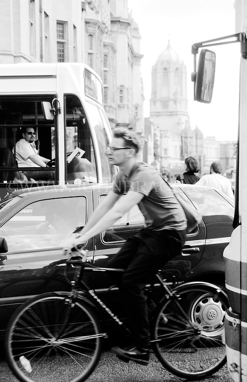 Black and white photo of a man on a bicycle on a busy street in Oxford, England.