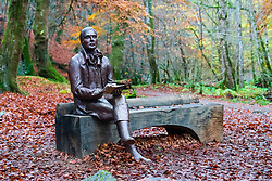 Statue of poet sits on outdoor Robert Burns on bench during autumn at the Birks O'Aberfeldy scenic area in Aberfeldy, Perthshire, Scotland,UK
