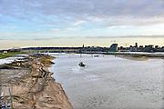 Nederland, Nijmegen, 10-12-2015 De bijna 4 km. lange nevengeul aan de overkant van de Waal bij Lent. Laatste werkzaamheden.  Grootste onderdeel van de vele werken van Rijkswaterstaat om bij hoogwater een betere waterafvoer in de rivier te hebben. In precies drie jaar is het werk uitgevoerd. Het is een omvangrijk project waarbij onder meer de pijlers van het spoorviaduct een bredere basis kregen omdat die straks in de loop van het water staan. De Waalbrug heeft een verlenging via een nieuwe brug met drie gracieuze pijlers. Het dorp veurlent komt op een kunstmatig eiland te liggen met twee kleinere bruggen als ontsluiting. Een voetgangersbrug naar het recreatiegebied en een andere, de Promenadebrug, voor normaal verkeer. Ruimte voor de rivier, water, waal. In de nieuwe dijk wordt een drempel gebouwd die stapsgewijs water doorlaat en bij hoogwater overloopt. The Netherlands, Nijmegen Measures taken by Nijmegen to give the river Waal, Rhine, more space to flow during highwater and to prevent the risk of flooding. Room for the river. Reducing the level, waterlevel. Large project to create a new paralel gully, an extra flow of water, so the river can drain more water during highwater. Due to climate change and expected rise, increase of the sealevel, the Dutch continue to protect their land from the water. Foto: Flip Franssen/HH