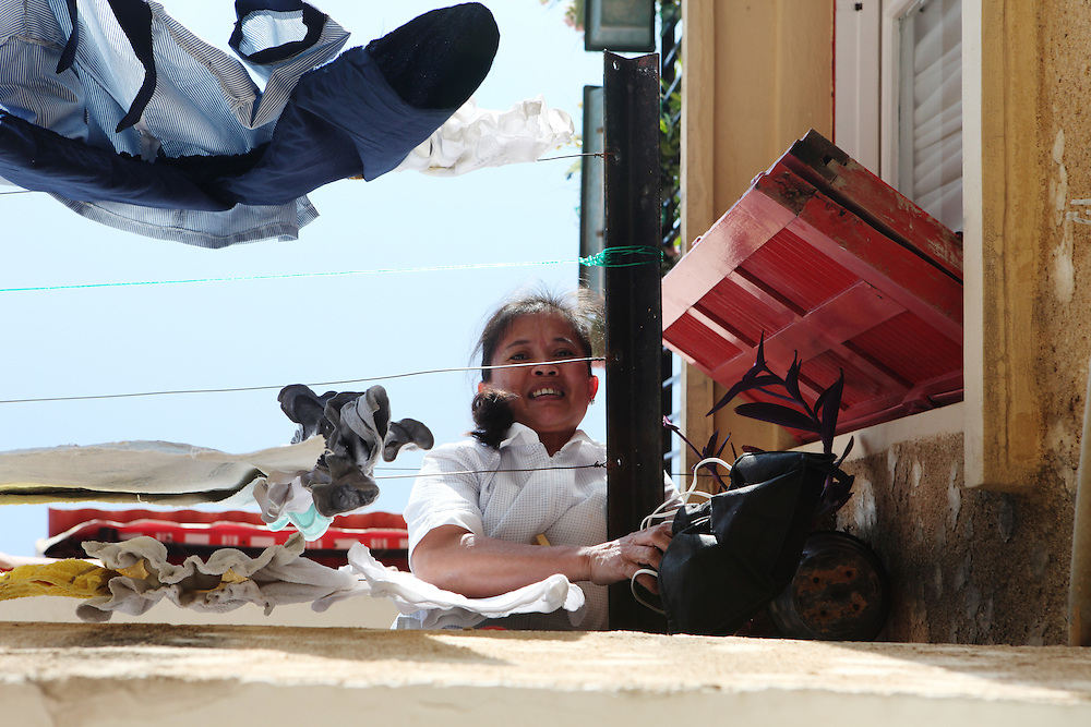 Balcony talk: Filipino women communicate from the balconies of their employers' homes. Since many women are prevented from leaving their homes they are forced to find different ways in order to communicate with other workers.