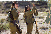 Female Israeli soldiers check their targets at a shooting range