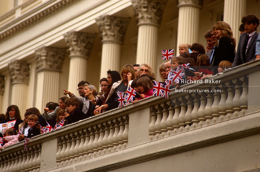 Beneath Corinthian pillars and columns, members of English society look down from a balcony during the annual Trooping of the colour parade in the Mall. From their high vantagepoint, this high-society watches a parade of armed services members as they march past towards the nearby parade ground at Horseguards. Waving patriotic union jack flags, children join in the euphoria on this royal annual event, an occasion on the summer season's calendar. The Sovereign's birthday is officially celebrated by the ceremony of Trooping the Colour on a Saturday in June.