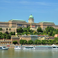 Brief History of Buda Castle in Budapest, Hungary <br /> The Buda Castle majestically watches over the Danube from the top of Castle Hill. The 1,000 foot long Royal Palace is a testament to Hungarian history. Béla IV, who was King of Hungary and Croatia from 1235 to 1270, was the first to build a castle on the west bank as part of a defense against devastating Mongolian invasions. In 1361, Buda became the country's capital. While the King of Hungary (1387 – 1437), Holy Roman Emperor Sigismund of Luxemburg spent lavishly to enlarge the castle. Next King Mátyás expanded it in the second half of the 15th century. In 1686, Buda Castle was destroyed during the siege by the Holy League's army, partially rebuilt by the Hapsburgs in the early 18th century and then engulfed in flames in 1849 during the War of Independence. In 1891, architect Alajos Hauszmann was commissioned to give the castle a Neo-Baroque design. During WWII, the Germans used Budavári Palota as a stronghold until brutally attacked by the Russians in 1945. The reconstruction you see today reflects elements of these 750 years of historical events.