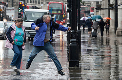 © licensed to London News Pictures. London, UK 11/06/2012. A man jumping over a large puddle onto the pavement in Regent Street, today (11/06/12). Photo credit: Tolga Akmen/LNP