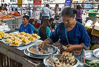 YANGON, MYANMAR - CIRCA DECEMBER 2013: Portrait of Burmese woman selling bread and pastries in the streets of Yangon