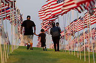 A family walk through amongst 3,000 US flags are displayed at Pepperdine University to mark the 12th anniversary of the 9/11 terror attack, September 10, 2013 in Malibu, California. Photo by Ringo Chiu/PHOTOFORMULA.com)