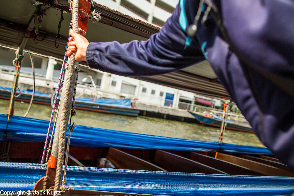 14 NOVEMBER 2012 - BANGKOK, THAILAND: A member of a boat crew boards her boat at the Wat Sriboonreung Pier, the southern terminal of the Khlong Saen Saeb boat service. Bangkok used to be criss crossed by canals (called Khlongs in Thai) but most have been filled in and paved over. Khlong Saen Saeb is one of the few remaining khlongs in Bangkok with regular passenger boat service. Boats and ships play an important in daily life in Bangkok. Thousands of people commute to work daily on the Chao Phraya Express Boats and fast boats that ply Khlong Saen Saeb. Boats are used to haul commodities through the city to deep water ports for export.      PHOTO BY JACK KURTZ