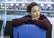 Frau wartet mit Koffer, hoert Musik, Flughafen Muenchen (model-released)