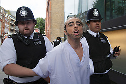 © licensed to London News Pictures. London, UK 02/08/2012. A FEMEN protester being arrested by police officers outside the City Hall as demonstrators wanted to protest against Islamic regimes which they claim are supported by the Olympic Committee. Photo credit: Tolga Akmen/LNP