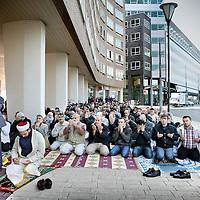 Nederland, Amsterdam , 1 oktober 2010..Turkse moslims bidden tijdens vrijdagmiddaggebed op straat op het Bos en Lommerplein uit protest tegen uitzetting van hun gebedshuis, de tijdelijke moskee oftewel kraakmoskee in een kantoorpand aan de overkant..Turkish Muslims pray outside on the streets during Friday prayers at the Bos en Lommerplein  in protest against removal of their house of worship.