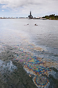 Leaking fuel from the USS Arizona in Pearl Harbor forms a slick on the surface of the water in front of the USS Missouri.