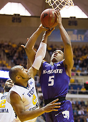 Feb 11, 2017; Morgantown, WV, USA; Kansas State Wildcats guard Barry Brown (5) shoos under the basket and is defended by West Virginia Mountaineers guard Jevon Carter (2) during the first half at WVU Coliseum. Mandatory Credit: Ben Queen-USA TODAY Sports