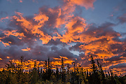 Orange sunrise light spotlights clouds over Kananaskis Country, Canadian Rockies, Alberta. Access the Mt Kidd Interpretive Trail from Mt Kidd RV Park. Kananaskis Country is a park system west of Calgary.