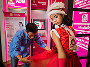 17 SEPTEMBER 2015 - BANGKOK, THAILAND:  A participant in the Santa pageant gets help with her costume at the World Santa Claus Congress. Twenty-six Santa Clauses from around the world are in Bangkok for the first World Santa Claus Congress. The World Santa Claus Congress has been an annual event in Denmark since 1957. This year's event, hosted by Snow Town, a theme park with a winter and snow theme, hosted the event. There were Santas from Japan, Hong Kong, the US, Canada, Germany, France and Denmark. They presented gifts to Thai children and judged a Santa pageant. Thailand, a Buddhist country, does not celebrate the religious aspects of Christmas, but Thais do celebrate the commercial aspects of the holiday.    PHOTO BY JACK KURTZ