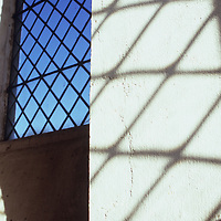 Shadow of diamond-leaded window on white painted wall next to another diamond leaded window showing blue sky