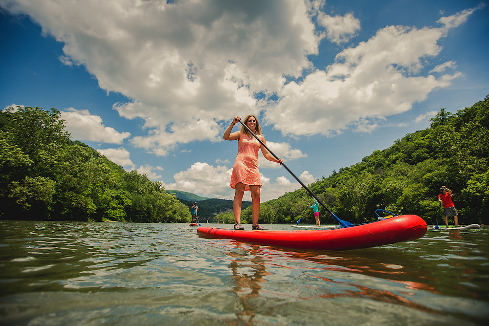 Men and women paddle boarding and camping on the New river in Virginia, in the heart of the Blue Ridge Mountains. Women woman hiking, biking, backpacking, adventuring, camping, paddle boarding outdoors,