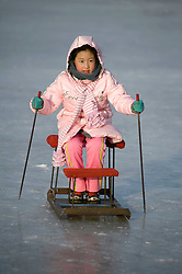 Young girl on old fashioned sled on frozen Songhua River in Harbin China during winter 2009