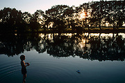 A young boy creates ripples as he plays with his radio-controlled boat in the River Thames at Dorchester, Oxfordshire. The sun is hidden behind a line of trees and the boy who is backlit stands in the shallow part of the river up to his ankles, wearing his swimming costume. The small boat is only a few feet from the antenna that controls its movement. It is a scene of idyllic tranquility, a childhood of happy summer days. Here the Thames is at its most serene, where visitors enjoy its shallows with the fear of strong currents, tides or large boating activity.