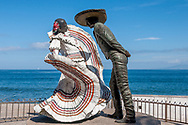 Bailarines de Vallarta or Dancers of Vallarta bronze sculpture on the malecon of Puerto Vallarta, dancing the Mexican Hat Dance. The Bay of Banderas is in the background, no people are in view.