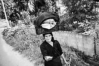 PISCOPIO (VV) - 7 SETTEMBRE 2018:  Una signora trasporta frutta e verdura in una cesta sulla testa a Piscopio, alle porte di Vibo Valentia,  il 7 settembre 2018.