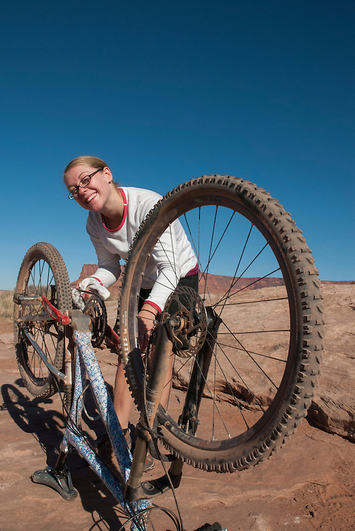 A woman in her early twenties mountain bikes the White Rim Trail near Moab, Utah.
