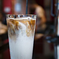 An iced coffee or iced latte in a large glass on a black counter