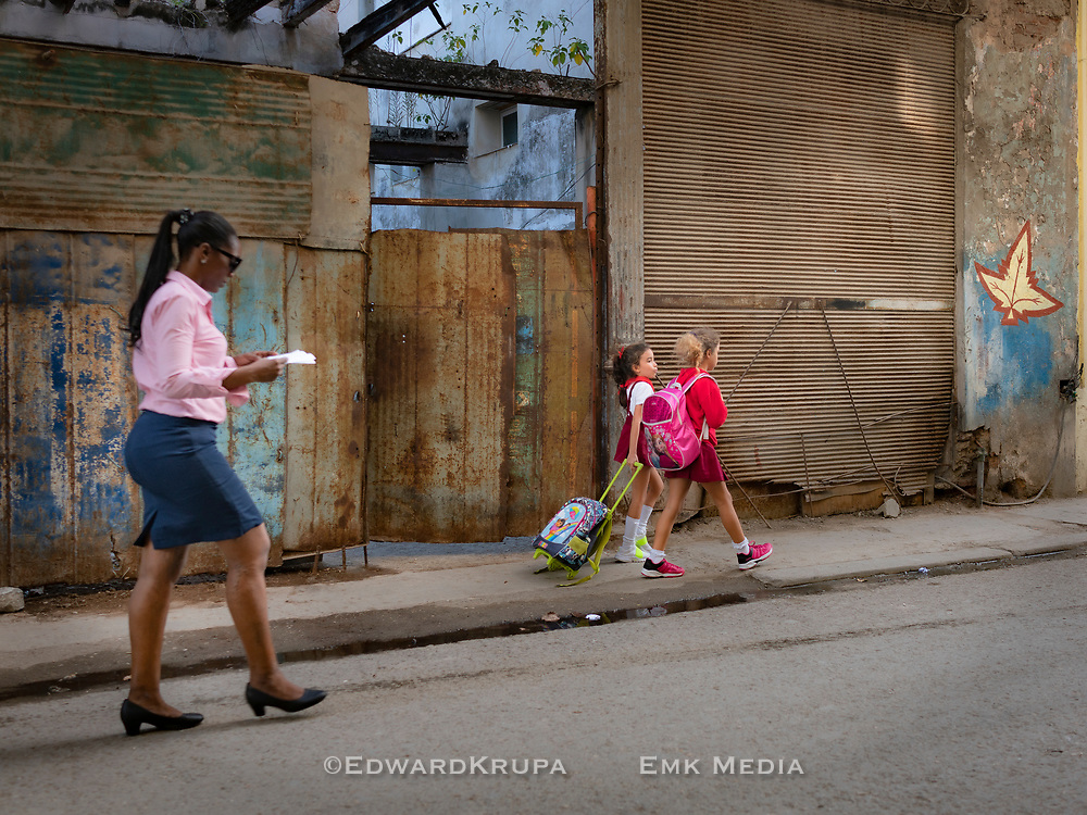 Two girls with school bags, talking while walking home from school on a street in Old Havana.