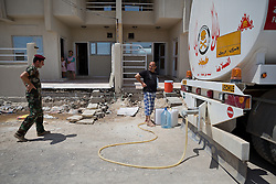 © Licensed to London News Pictures. Hamdaniyah, Iraq. 26/07/2014.  An Iraqi Christian refugee from Mosul talks to a Kurdish Zeravani solder  as he fills water containers from a tanker in Hamdaniyah, Iraq.<br /> <br /> <br /> <br /> Having taken over Mosul Iraq's second largest city in June 2014, fighter of the Islamic State (formerly known as ISIS) have systematically expelled the cities Christian population. Despite having been present in the city for more than 1600 years, Christians in the city were given just days to either convert to Islam, pay a tax for being Christian or leave; many of those that left were also robbed at gunpoint as they passed through Islamic State checkpoints.. Photo credit : Matt Cetti-Roberts/LNP