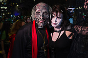 New York, NY - 31 October 2019. the annual Greenwich Village Halloween Parade along Manhattan's 6th Avenue. A clergyman and his consort, he with a lined face covered in lesions, she wearing leather and lace.