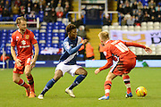 Birmingham City midfielder Demarai Gray skips past MK Dons forward Dean Bowditch and MK Dons midfielder Ben Reeves during the Sky Bet Championship match between Birmingham City and Milton Keynes Dons at St Andrews, Birmingham, England on 28 December 2015. Photo by Alan Franklin.